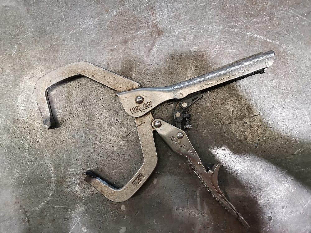 Metal vise grip clamp being used