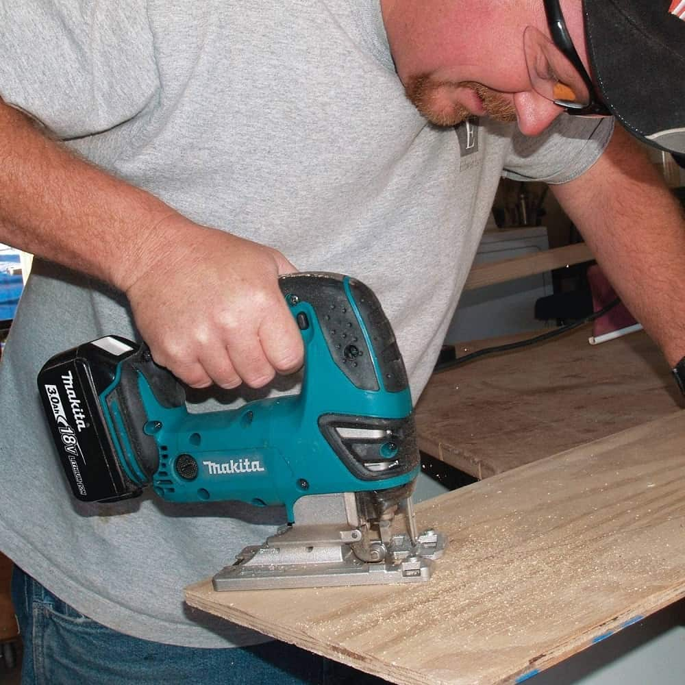 Man cutting plywood with cordless makita jigsaw