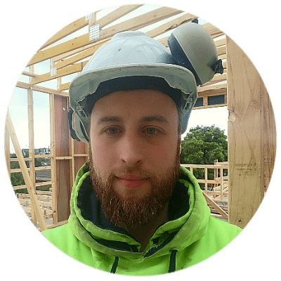 Aaron with hard hat on building site