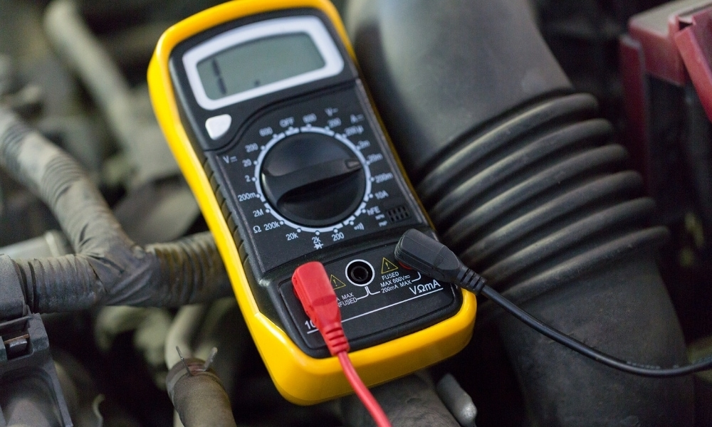 Using a digital multimeter on vehicle engine