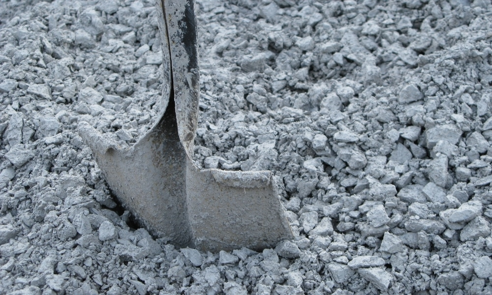 A cement and dirt covered gravel shove above gravel pile