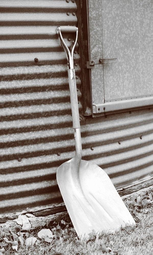 A grain shovel placed on a corrugated metal wall 1