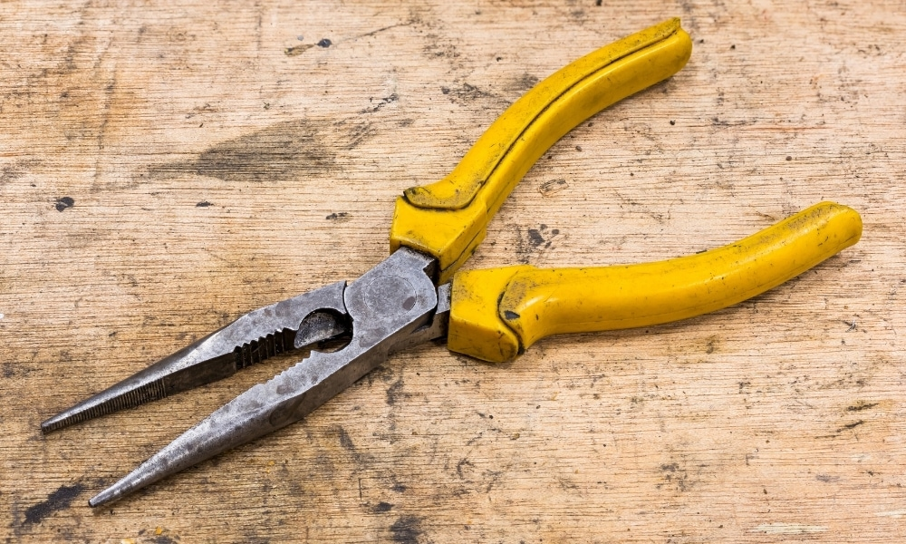 A needle nose or long nose pair of pliers with greased handles