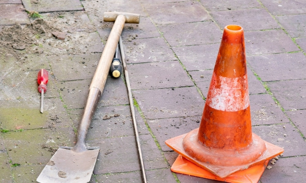A tile shovel used in construction on tiled outdoor floor