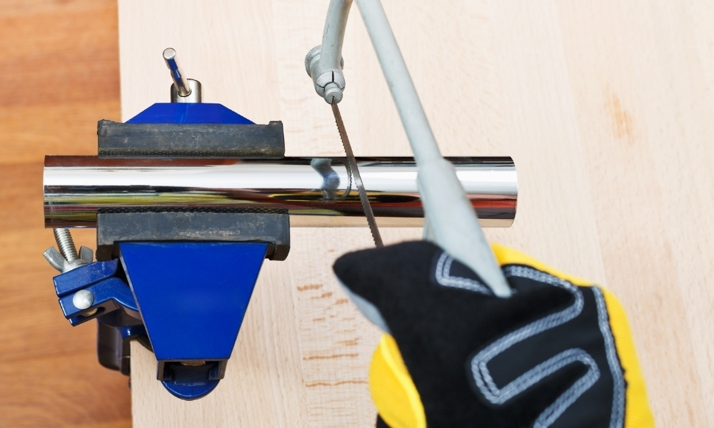 Cutting pipe with a saw and clamped bench vise