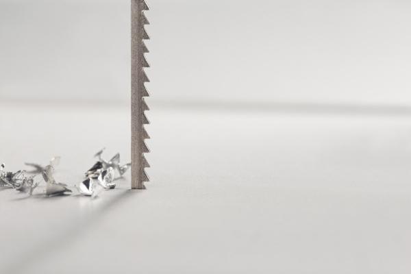 Jigsaw blade cutting an aluminum sheet