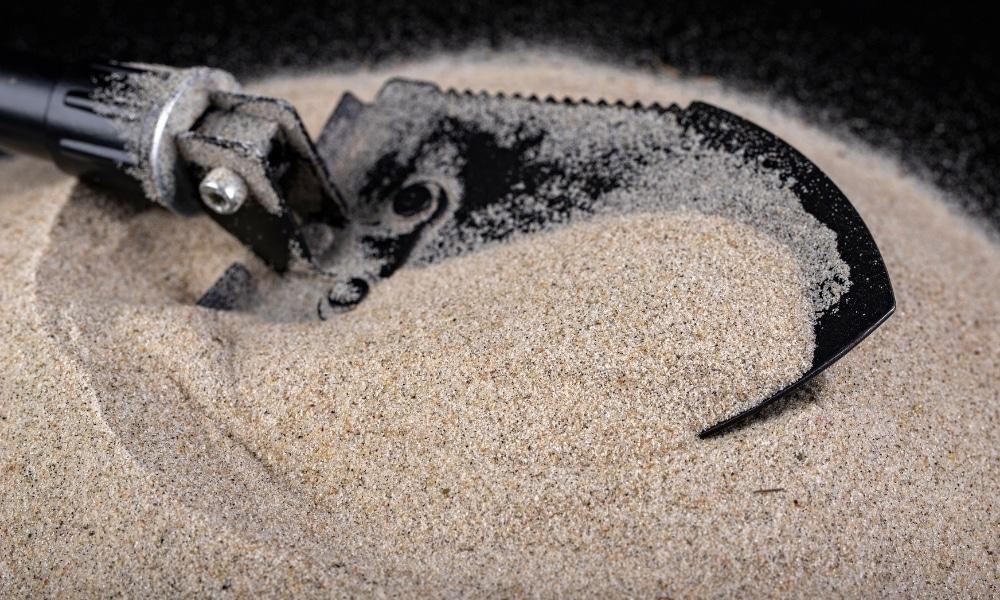 Military shovel scooping sands
