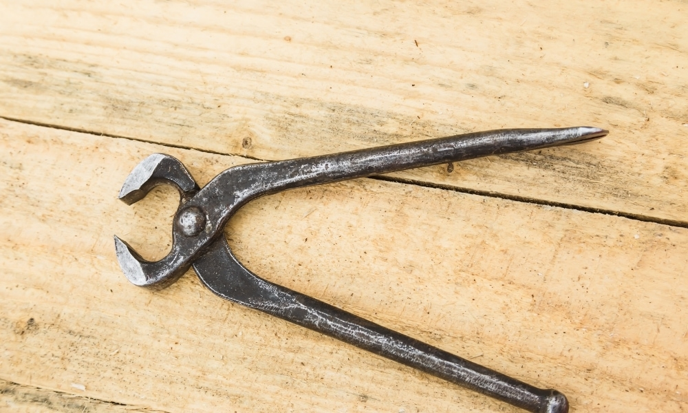 Pliers for nail pulling over a piece of wood