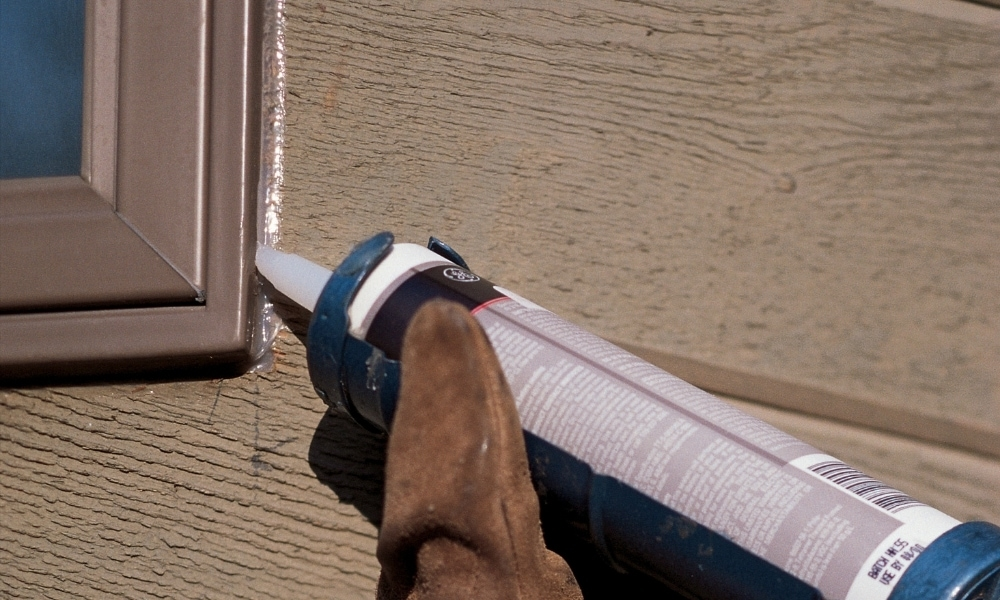 Putting caulk on the outside of a window frame