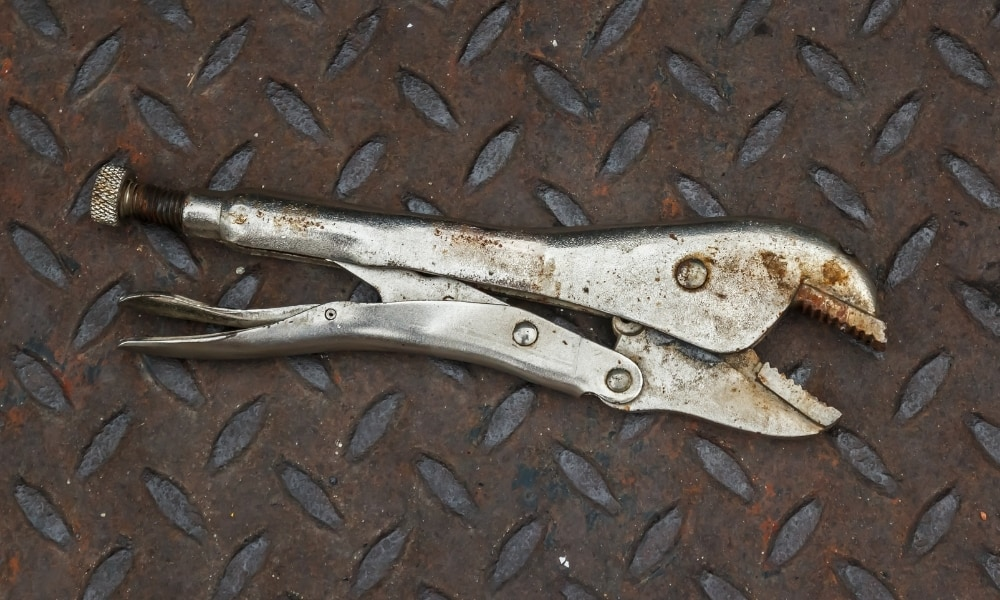 Rusty locking pliers placed over a steel ramp