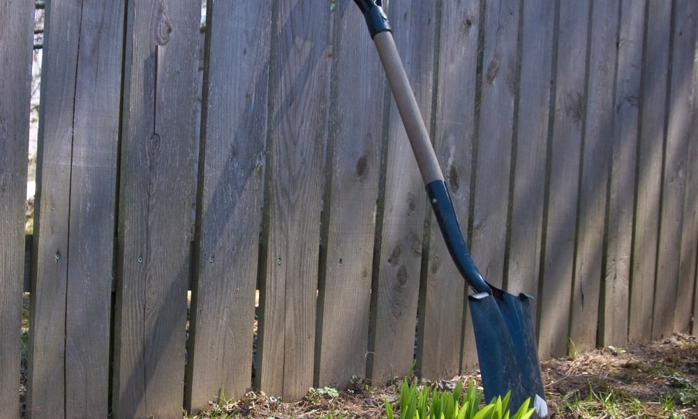 Square point shovel leaning on the fence