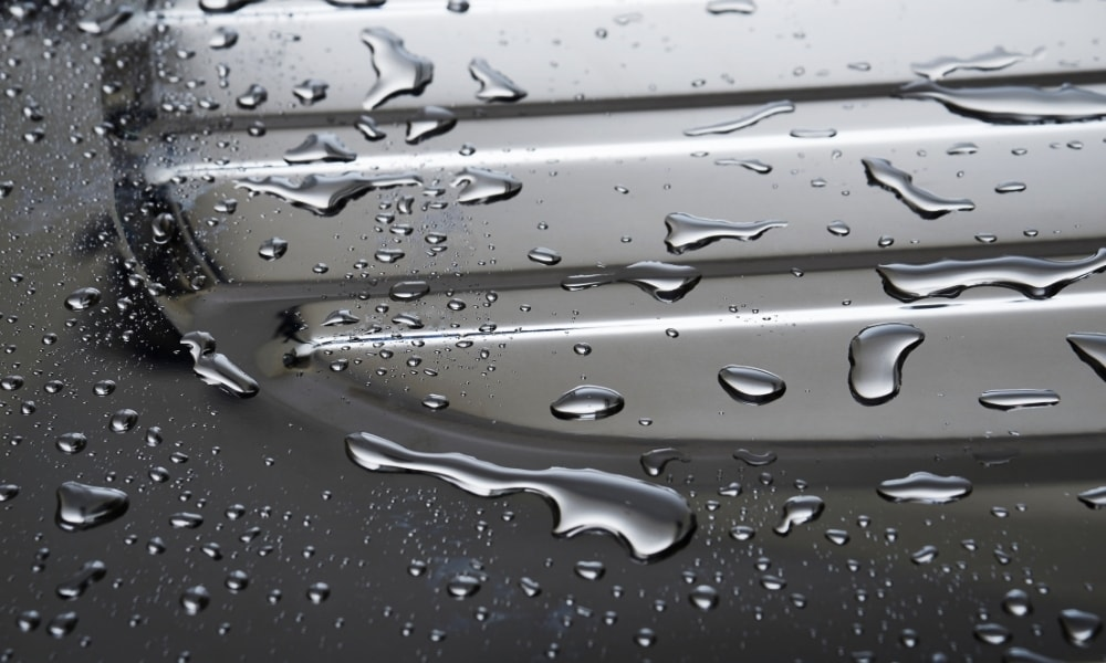 Waterdrops trying to get through a stainless steel surface