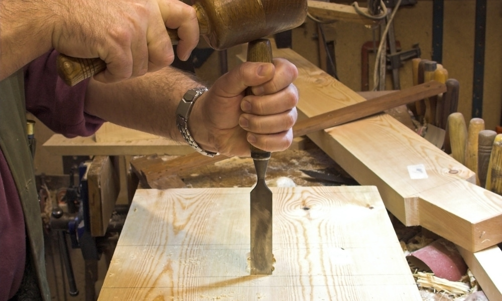Chopping a wood with chisel and a wooden mallet