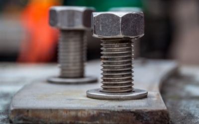 Two pieces of threaded bolt attaching wood to a concrete